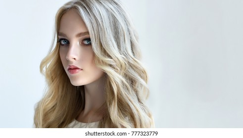 Blonde fashion  girl with long  and   shiny curly hair .  Beautiful  fashion model   with wavy hairstyle .Hairstyling tousled waves