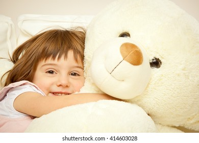 blonde female child play with her white teddy bear in a bed