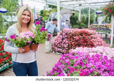 Blonde female customer in garden center while holding flowers