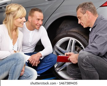 a blonde female customer squads with the two male car service employee at her car in front of the tire an talking about it, what repair or changing the car need