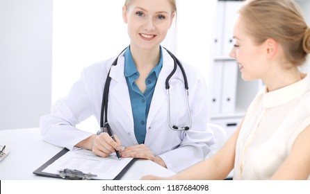 Blonde female doctor and patient talking in hospital office. Health care and client service in medicine
