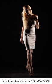 Blonde female dressed in night dress. Woman in nightie on black background.
