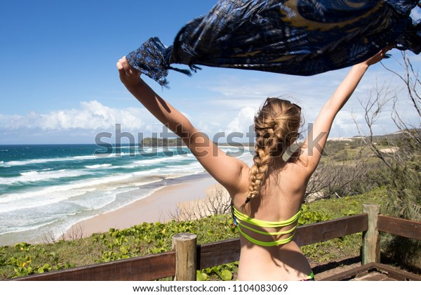 Blonde female girl arms up at beach lookout headland mountain in