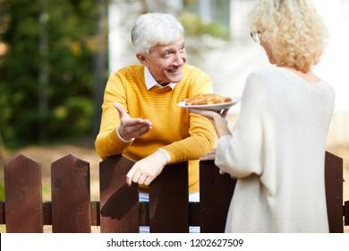 Femme blonde donnant à sa voisine un morceau de tarte aux pommes maison sur une barrière en bois