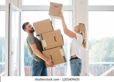 blonde female placing moving boxes on large stack man is holding all