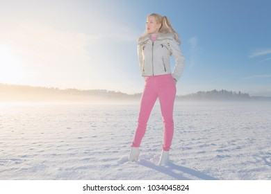 Blonde female in ponytails in a winter landscape wearing pink pants. Freezing cold and high heels on a field.
