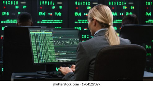 Blonde female programmer sits at computer in server room and works with database. System software concept. View from back.