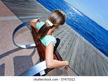 blonde female relaxing in a futuristic chair and enjoying the view to the seaside with sun reflexion