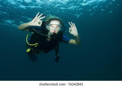 blonde female scuba diver in clear blue water