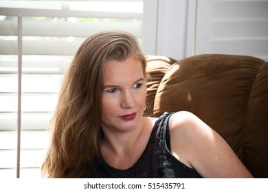Blonde Female Sitting On Couch in Front of Window Looking Away From Camera