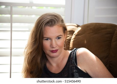 Blonde Female Sitting On Couch In Front of Window Looking Down