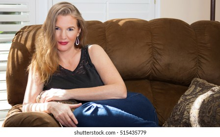 Blonde Female Sitting Relaxed On Couch