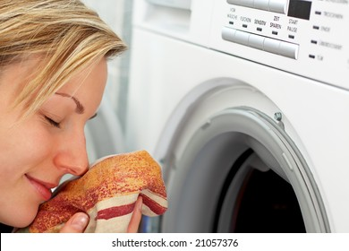 blonde female is smelling freshly washed laundry