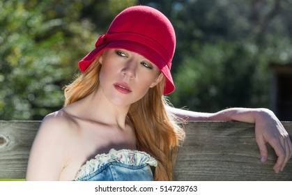 Blonde Female Wearing Red Hat with arm on fence in outdoor portrait shoot.