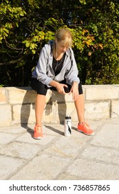 Blonde fitness female taking break from intense workout while listening to music.