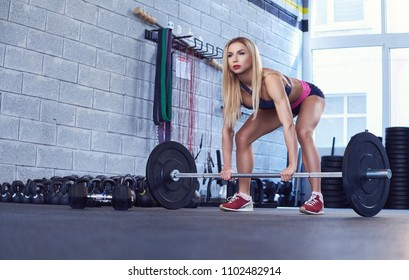 Blonde fitness sporty woman with a muscular body in a sportswear doing deadlift with a barbell at a gym.