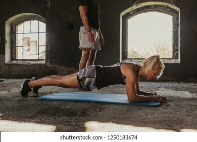 Blonde fitness woman doing plank in an old building while trainer standing beside her