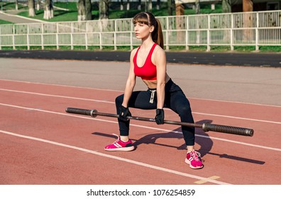 Blonde fitness woman is lifting a barbell outdoors at the stadium. Fitness woman does deadlift using barbell side view. Crossfit woman. Crossfit style.