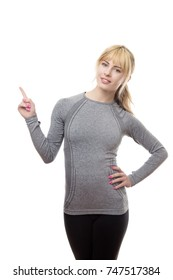 blonde fitness woman point up at something in the sky