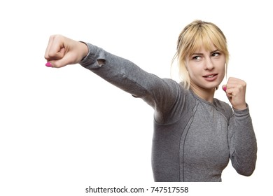 blonde fitness woman wearing a grey top punching the air