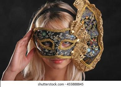 blonde flirts in the Venetian mask on black background