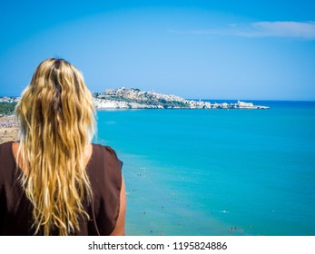 Blonde girl admires the Arco di San Felice, caves and beach, south of Vieste, Apulia, Italy. The Arch of San Felice, excavated by erosion, south of Vieste are the result of karstic phenomena
