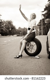 Blonde girl asks for help on the road near her broken car. Toned image