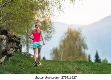 Blonde girl athlete runs a mountain path in the green grass