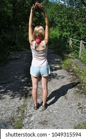 Blonde girl with bandana and shorts exercising outdoors near the fence and forest. Woman wearing sport sandals stretching in the middle of the road or pavement outside on sunny summer day. Fit person