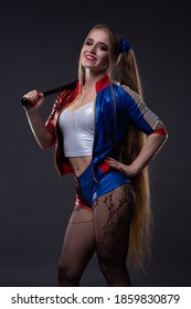 A blonde girl with a bat in her hands and a costume of the comic book hero Harley Quinn on a dark background