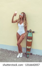 Blonde girl beautiful bathing suit body, with longboard board. Summer day city. Hand, smartphone, photographs self in social network, online app Internet. Tanned skin long hair. Woman happy smiling.