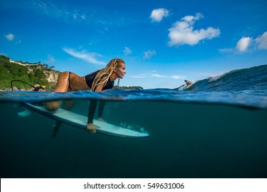 Blonde girl in black bikini - Surfer with white surfboard ready to dive under big ocean wave incoming Family lifestyle, people water sport lessons, beach extreme swimming activity on summer vacation