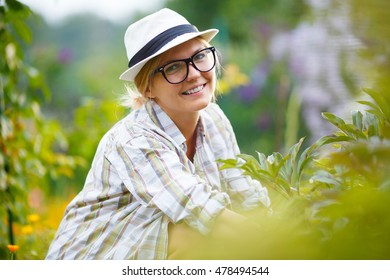 blonde girl in black glasses on background of plants