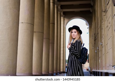 Blonde girl in black hat with backpack walking on the street. Woman standing in arch of classic colonnade building. City traveling alone concept.