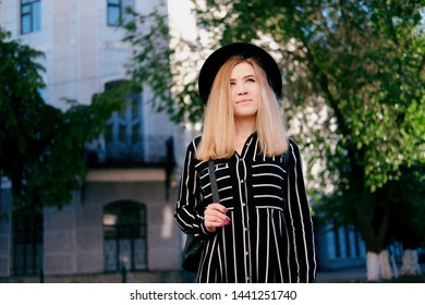 Blonde girl in black hat walking on the street. City traveling alone concept.