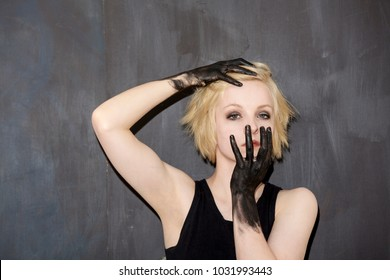 Blonde girl with black painted hands