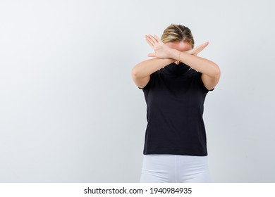 blonde girl in black t-shirt, white pants, black mask holding two arms crossed, gesturing no sign and looking harried , front view.