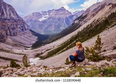 Blonde girl in black and white cloths is sitting watching deep mountain valley with trees and moraines on the sides. Stanley glacier trail in Kootenay national park in British columbia, Canada.