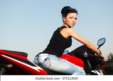 Blonde girl in blue dress with red chopper on bike festival.