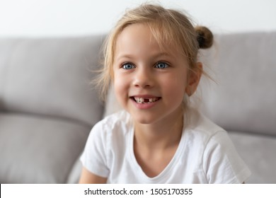 blonde girl with blue eye in a white t-shirt of a school-age without a front tooth laughs. Close-up. Change of teeth