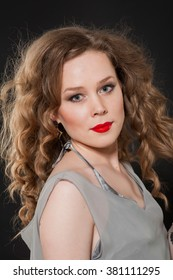 Blonde girl with blue eyes, long curly hair in a gray dress