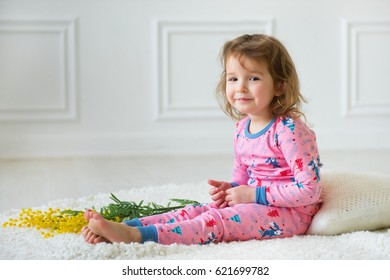 Blonde girl in bright pajamas on the white carpet