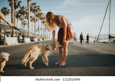 Blonde girl caring a cute dog in the street, close to the marina port at sunset.
