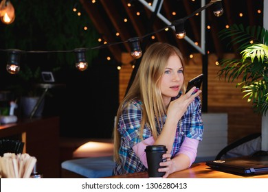 Blonde girl in casual clothes sends audio message using smartphone sitting in cozy hipster coffee shop. Voice mail technology