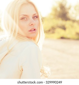 Blonde girl close-up portrait in sun-rays