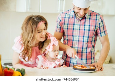 blonde girl is cooking with her parents in a luminous kitchen