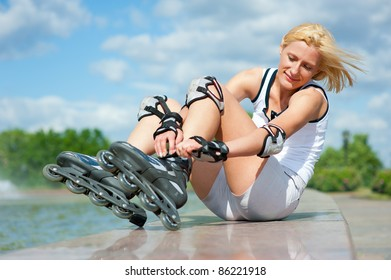 Blonde girl corrects the clasp of roller skates