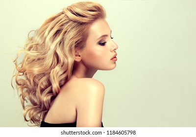 Blonde girl with curly hair. A volumetric hairstyle.