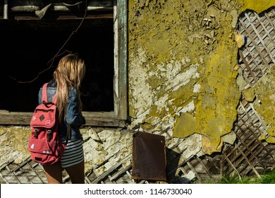 837334a7ac68 Blonde girl in a denim jacket with a red backpack explores an old abandoned  almost collapsed
