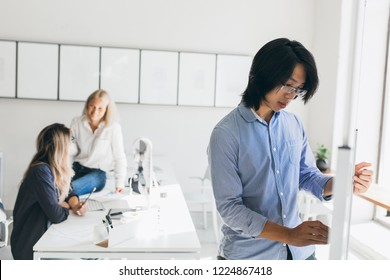 Blonde girl in denim pants sitting on table in office and talking with friend. Indoor portrait of young female secretary chilling at workplace and focused asian man on foreground.
